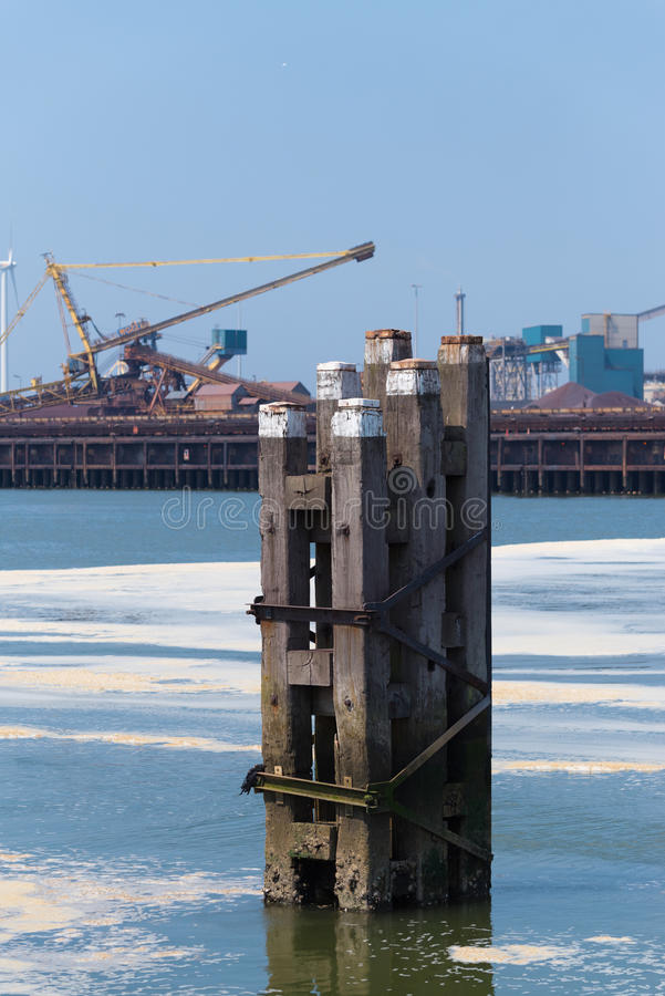 Waterway poles in harbor. Wooden poles that mark the waterway in front of a large steel plant royalty free stock photos