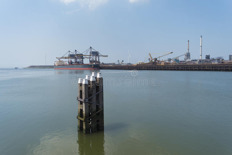Waterway poles in harbor. Wooden poles that mark the waterway in front of a large steel plant stock photo