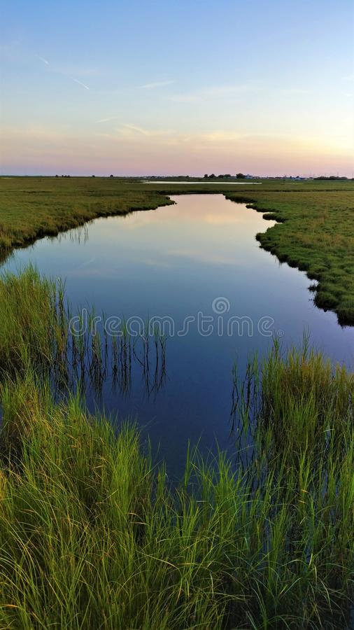 Waterway to eternity, Skanor Falsterbo, Scania, Sweden. Beautiful reflective waterway in Skanor Falsterbo, Sweden stock photo