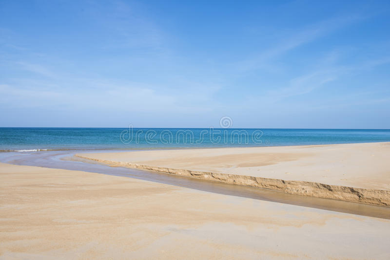 Waterweg die door het zand op strand vloeien stock foto