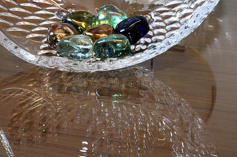 Watery stones , with a bowl reflection. A bowl of coloured stones, with a reflection of the bowl on the table. Fun colours, watery effect of the stones stock images