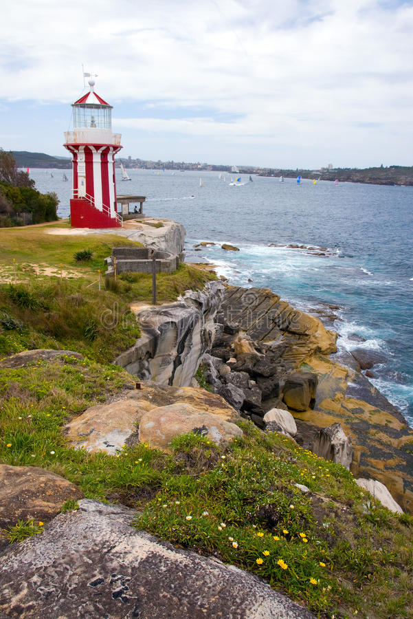 Watson Bay lighthouse. Coast scenery with red white striped lighthouse, rocks, bloom flowers and Manly shore and many sailboats on the background. Watson Bay stock photos