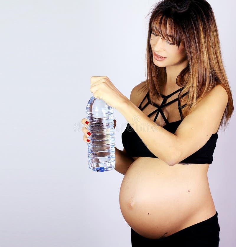 Watter bebendo da mulher gravida bonita da garrafa fotografia de stock