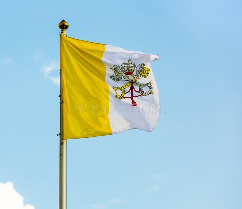 Watykan flaga przeciw niebieskiemu niebu obrazy stock