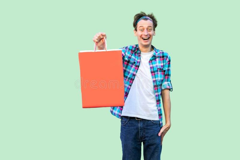 Wauw! Geschokte moderne jonge volwassen hipstermens in witte t-shirt en geruit overhemd die en het winkelen zakken bevinden zich  royalty-vrije stock fotografie