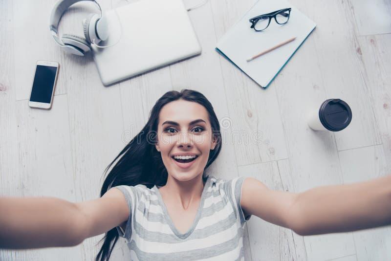 Wauw! Het verbaasde jonge leuke meisje maakt selfie op de vloer Zij I royalty-vrije stock foto