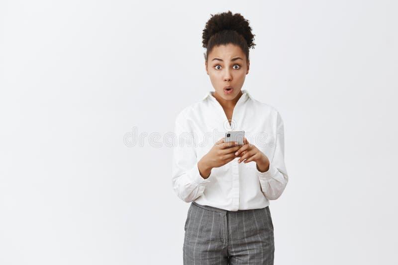 Wauw nieuwe eigenschappen na update Portret van nieuwsgierige leuke Afrikaans-Amerikaanse vrouw in elegante witte overhemd en bro royalty-vrije stock foto