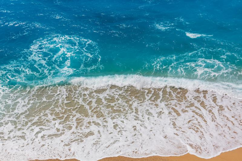 Wave. Blue wave on the beach. Blur background and sunlight spots. Peaceful natural background royalty free stock photo