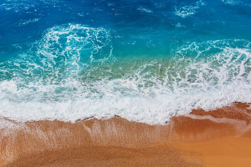 Wave. Blue wave on the beach. Blur background and sunlight spots. Peaceful natural background stock image