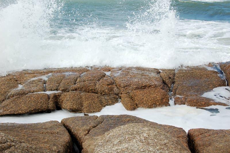 wave break on rocks stock photos
