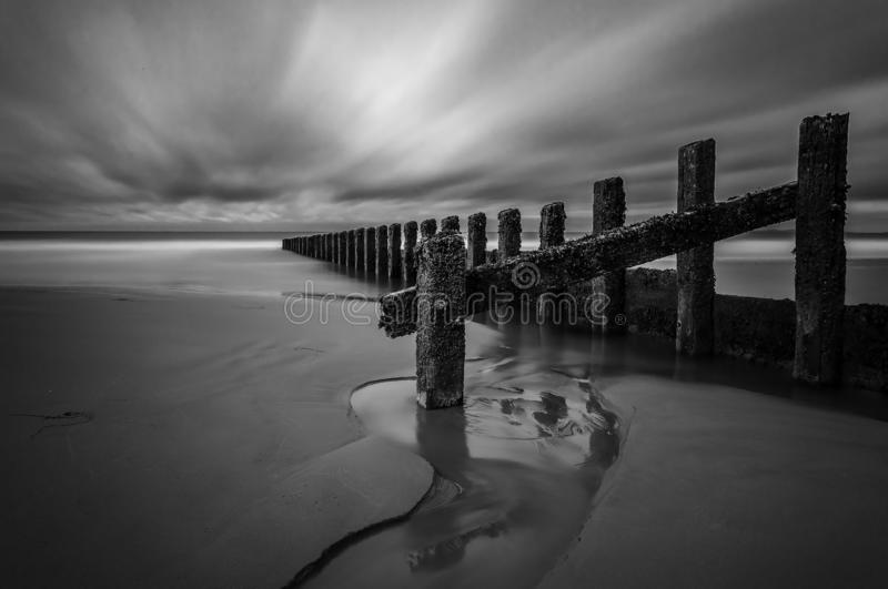 Wave Breaker. Fine Art Long Exposure Monochrome, Wave Breaker as part of the coastal sea defences around the UK Coastline. In the popular seae town of Barmouth royalty free stock photography