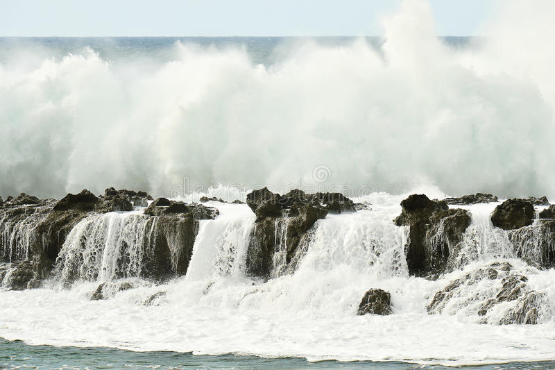 Wave Breaking above Rock Wall on Clear Day royalty free stock images