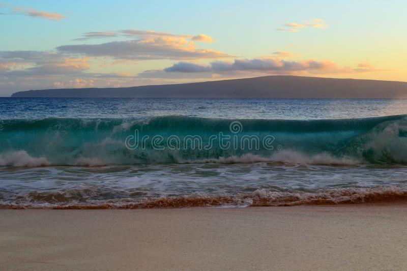 Wave breaking on beach. Wave breaking close to beach in Hawaii, front view stock image
