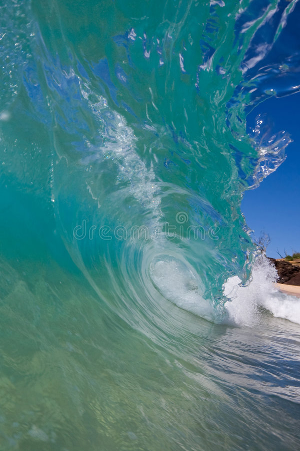 Wave Breaking By Beach, In The Tube. View from inside the tube of a blue wave, a surfers dream royalty free stock photography