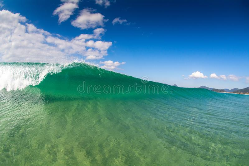 Wave breaking in crystal clear waters on the beach in Florianopolis Brazil. A wave breaks empty in clear waters on the beach at Florianopolis Brazil stock photo