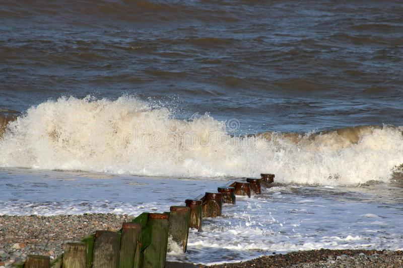 Wave breaking on shore by wooden groyne, Fleetwood royalty free stock photography
