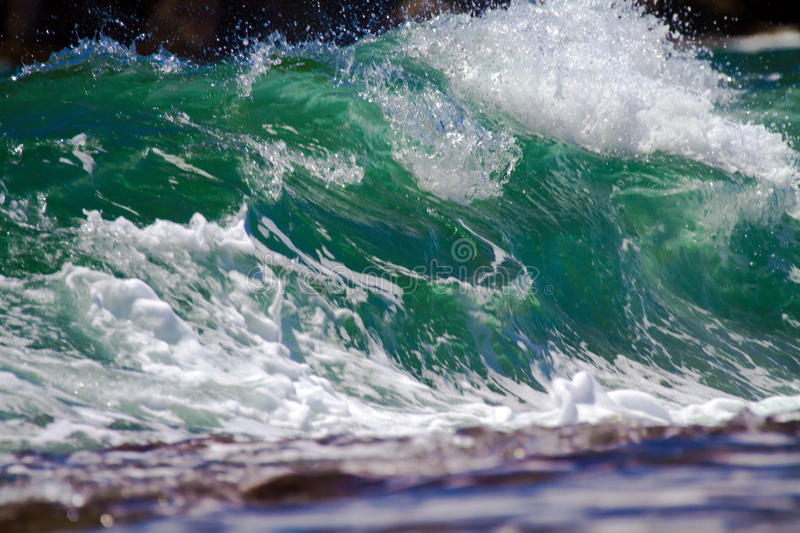 Wave Breaking On Shore. A wave breaking onshore on the coastline in Kauai, Hawaii stock images