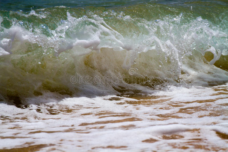 Wave Breaking On Shore. A wave breaking onshore on the coastline in Kauai, Hawaii royalty free stock image