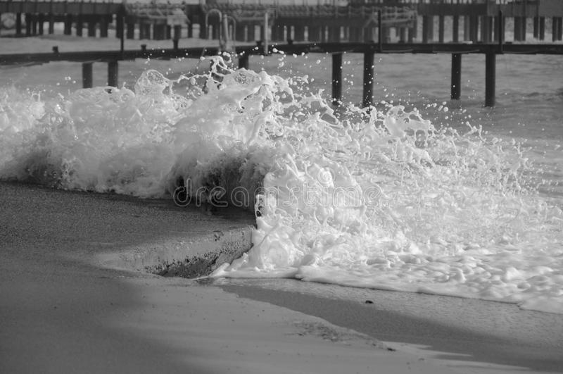The wave breaks against the shore for small drops and foam stock image