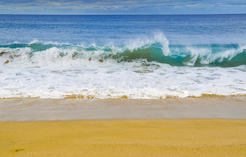 Wave breaks on Pacific Ocean beach. Clear, blue, waves break on the shore of a Pacific coast beach in Baja California Sur Mexico royalty free stock images
