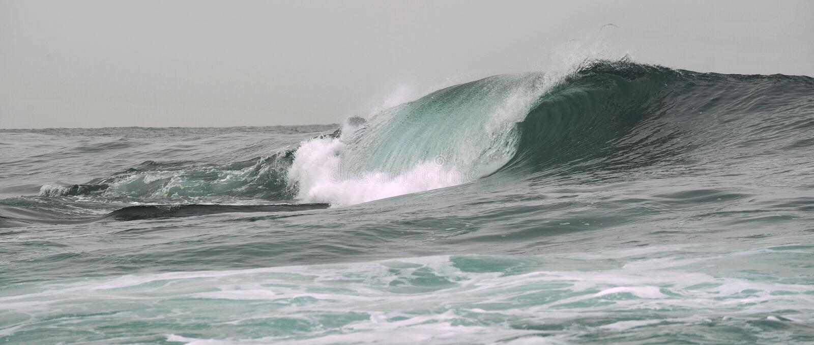 Wave breaks on a shallow bank. Wave on the surface of the ocean. Wave breaks on a shallow bank stock photography