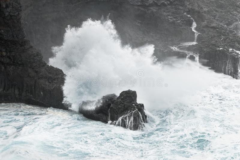 A wave breaks in stormy weather on a rocky coast stock image