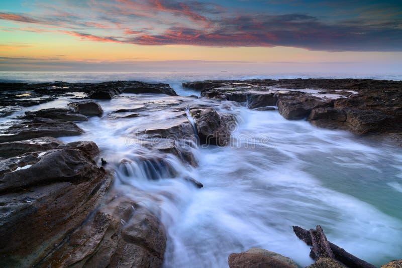 Wave circola sulle rocce stagionate e sui massi immagini stock