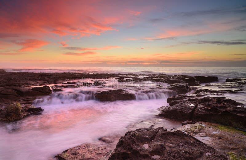 Wave circola sulle rocce stagionate e sui massi immagini stock libere da diritti
