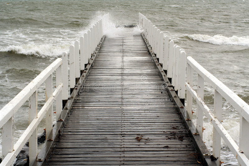 Wave crashes along a jetty royalty free stock images