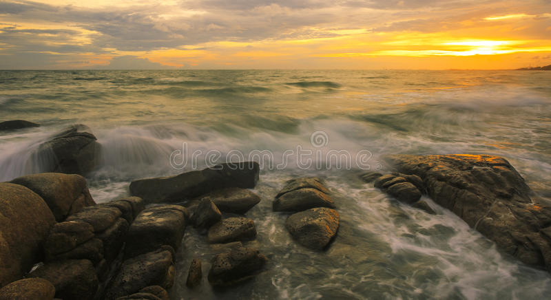 Wave crashes down onto the rocks. Waves hitting round rocks and splashing with sunset royalty free stock images