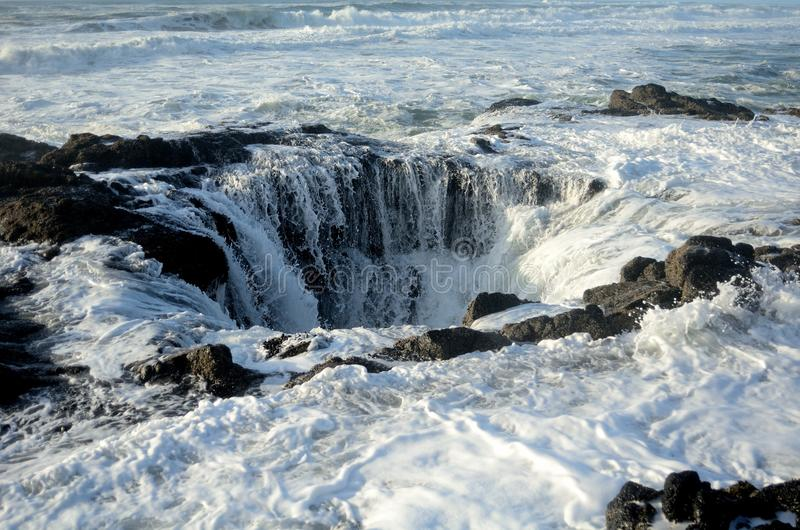 Wave Crashes Down Thor's Well. Ocean water from wave surges down Thor's Well royalty free stock photos