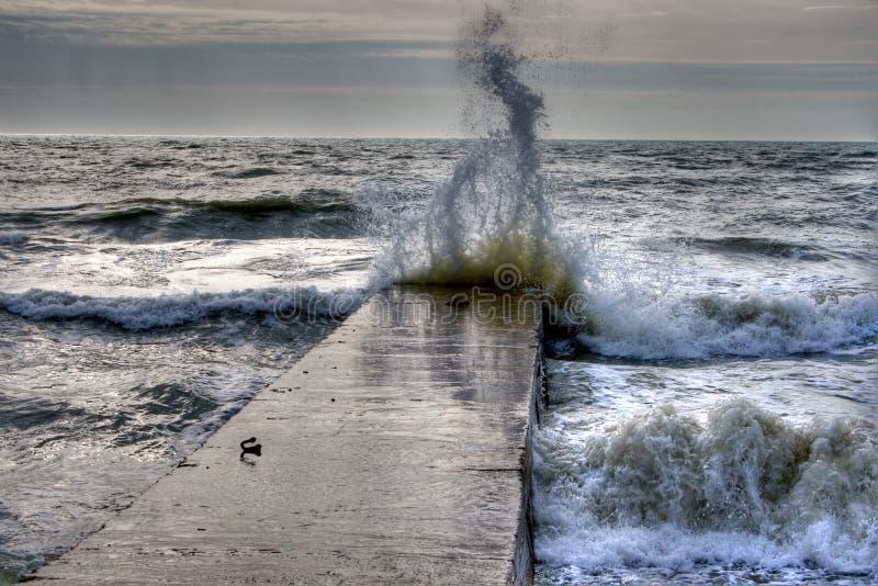 Wave crashing on breakwater royalty free stock photography