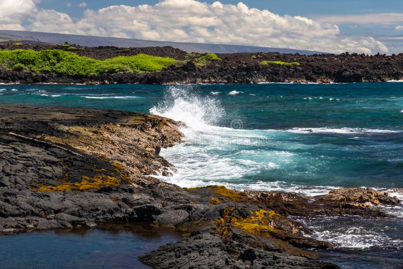 Black sand beach, wave crashing on black rocks. Big island of Hawaii. royalty free stock photos