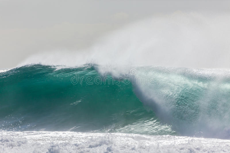 Wave Crashing. Ocean wave hollow crashing water power from weather storms royalty free stock photo