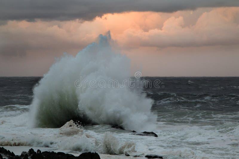 Wave crashing onto rock causing a big splash stock image