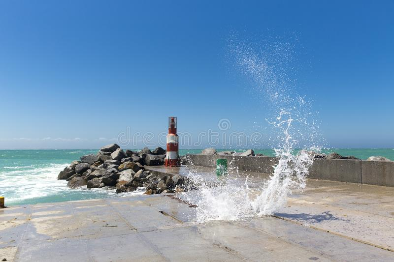 Wave crashing on pier at L`Agulhas bay South Africa royalty free stock photography