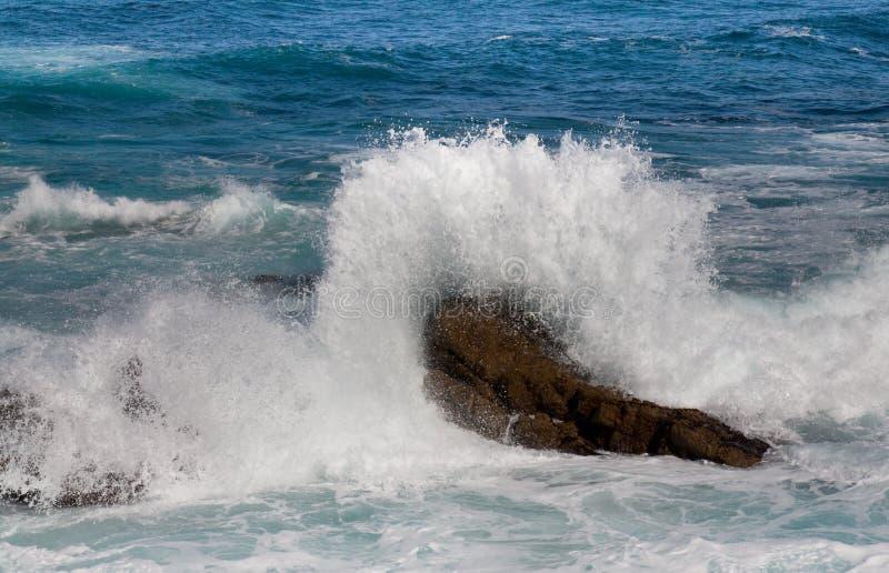 Wave crashing on the rock stock photos