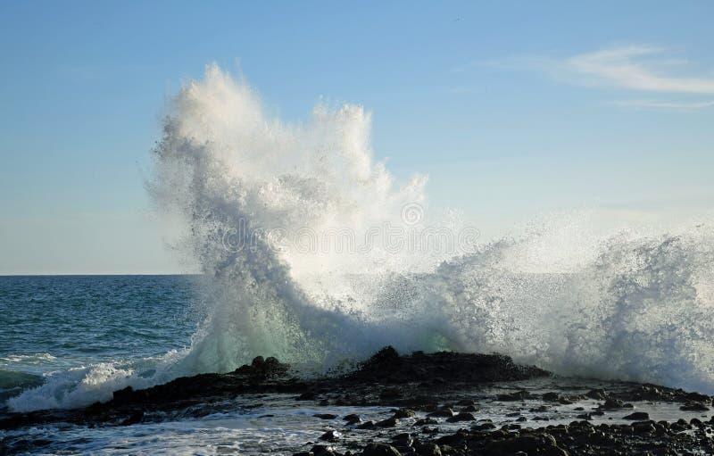Wave crashing on rocks at West Street Beach in South Laguna Beach,California. Image shows an evening view of a wave crashing on rocks at West Street Beach in stock photography