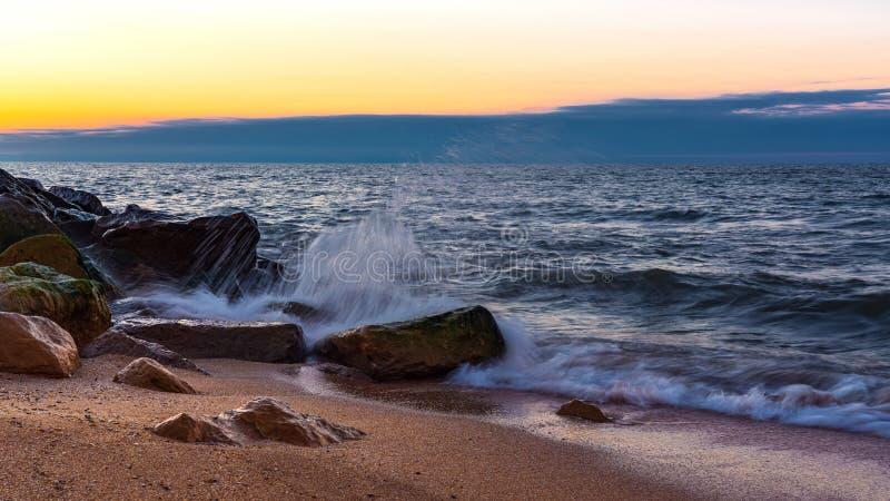 Wave crashing on the rocky seashore at sunset time. Scene royalty free stock photography