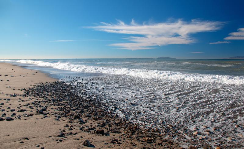 Wave foam washing over gravel on beach at McGrath State Park in Oxnard California USA. Wave foam washing over gravel on beach at McGrath State Park in Oxnard royalty free stock images