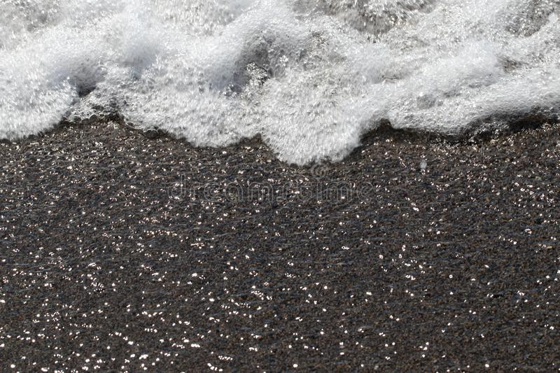 Wave foaming on the sand. Closeup of sea waves with white foam on the sandy shore with sun reflections effect stock photos