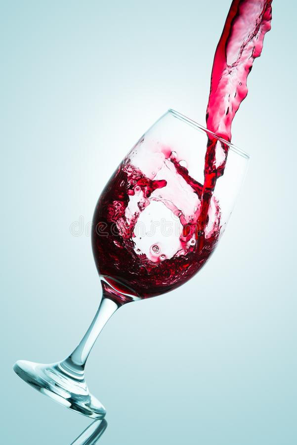 Wave formed on the pouring of red wine on a tasting glass stock photos