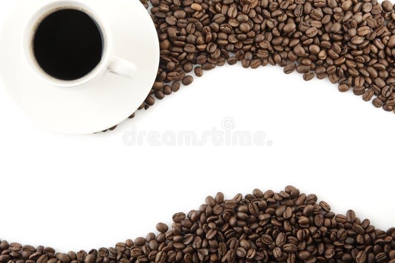 Wave ha fatto dei chicchi di caffè con la tazza di caffè fotografie stock libere da diritti