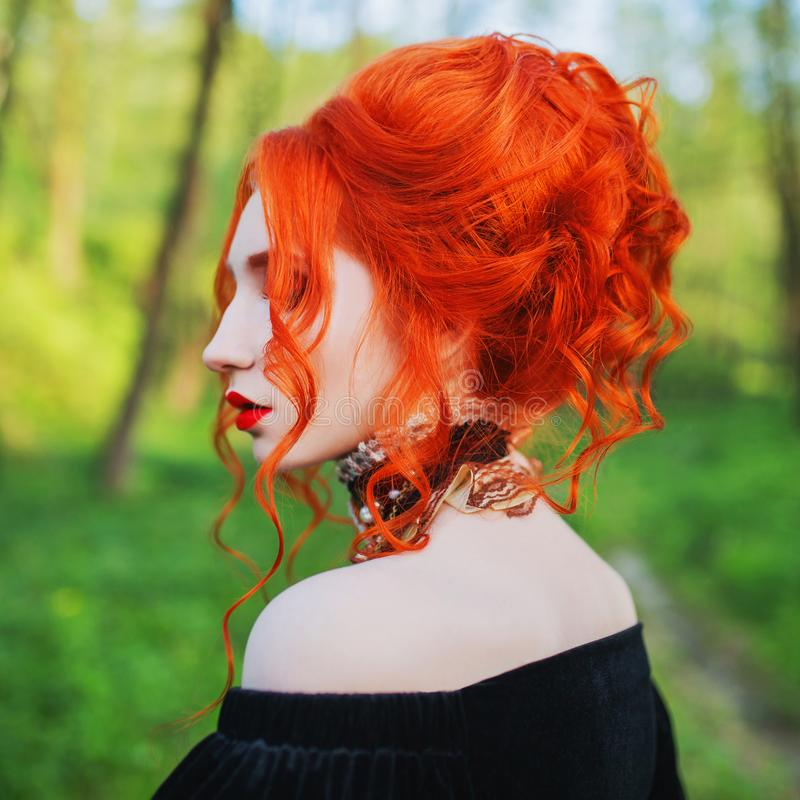 Wave hairdo in salon. Stylish halloween hairstyle. Gothic redhead woman is vampire with pale skin and red hair in dress and neckla. Ce on neck. Gothic hairstyle royalty free stock photography
