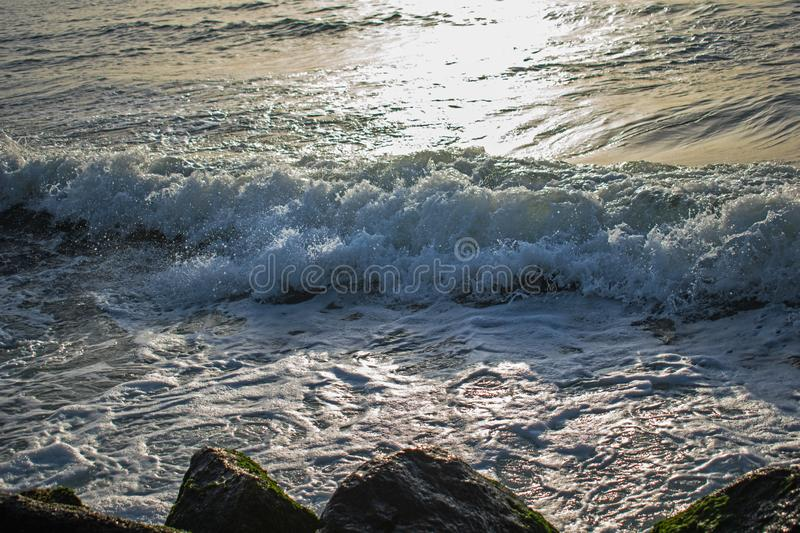 A wave with a lot of foam approaches the seashore by striking the stones stock photos