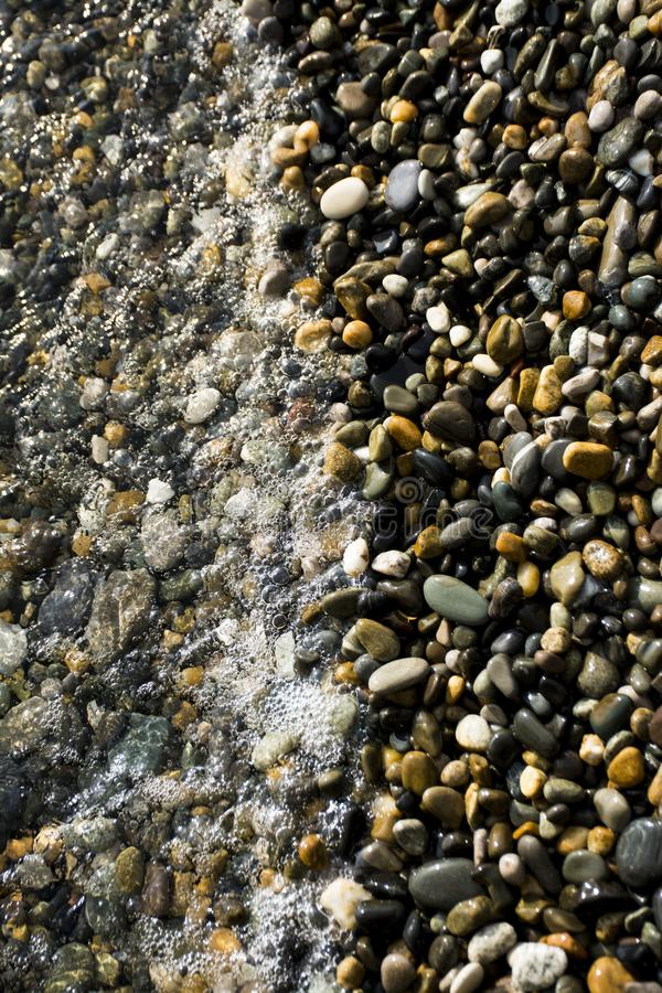 Wave and pebbles royalty free stock image