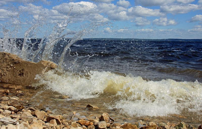 The wave of the river Volga. The wave of the river with splashes fell upon the stony bank of the river in the Kuibyshev reservoir of the river Volga Samara stock image