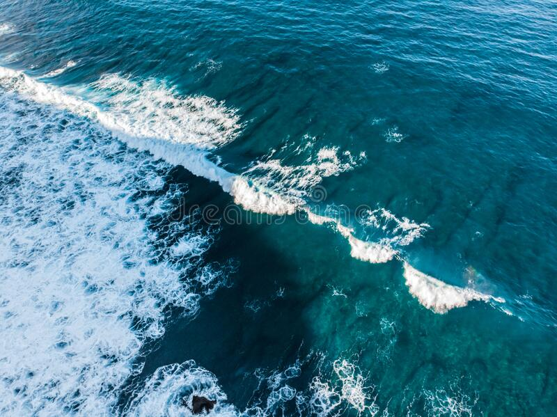 Wave rolls on the reef aerial view. A reef near the coast of the island of Bali under clear azure ocean water. Bukit Peninsula. Wave rolls on the reef aerial stock photos