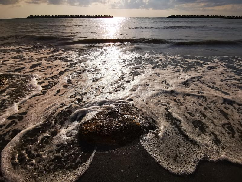 Wave on the sand beach. Wave that broke at the shore in the sunlight stock images