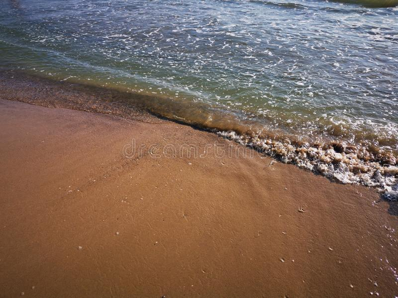 Wave on the sand beach. Sand with scraps of shells and the wave that broke at the shore in the sunlight royalty free stock photography